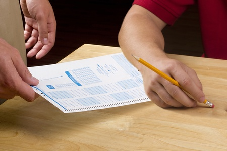Teacher handing a test to a student with a pencil. Stock Photo - 9401808