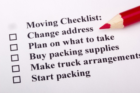 A red pencil laying on a Moving Checklist.