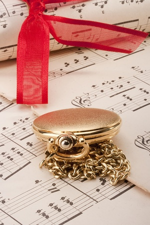 Theme music, old musical notes with old clocks and roll bandaged red ribbon. Stock Photo - 9487525