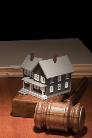 Gavel and house model in front of a stack of manila folders.