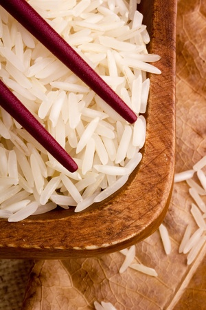 basmati: Close-up of white rice in a brown plate and red chopsticks.