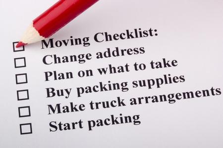 Red pencil checking a box on a Moving Checklist. Banco de Imagens