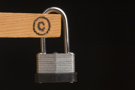 lock symbol: Copyright symbol on a piece of wood attached to a lock on a black background.