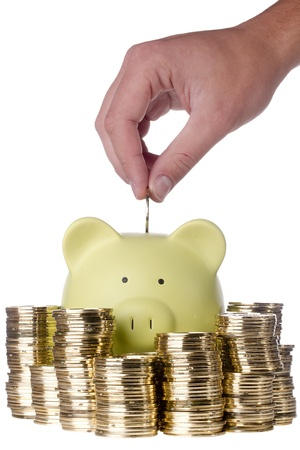 assets: Human hand putting a golden coin into a green piggy bank that is surrounded by stacks of golden coins on a white background. Stock Photo