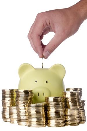 fondos negocios: Mano puesta una moneda de oro en una hucha verde que est� rodeada por las pilas de monedas de oro sobre un fondo blanco.