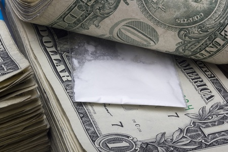 Small sealed bag with drugs laying in a stack of cash. photo