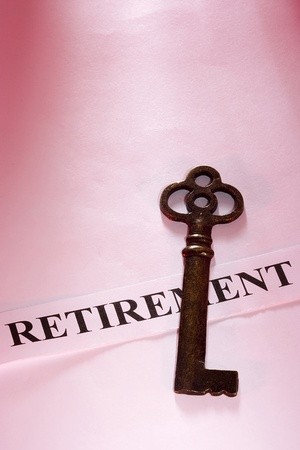 A key laying on a piece of paper with the word retirement on it. Stock Photo