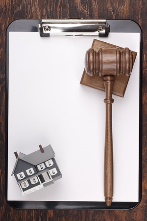 foreclosure: Justice gavel and house model on a clipboard. Add your text to the paper. Stock Photo