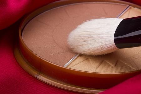 パウダー ブラシと赤の背景に茶色のパウダー。 写真素材