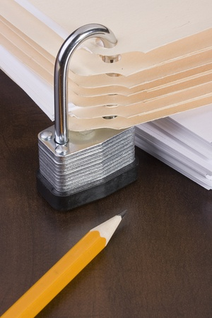 secure: Stack of manila folders closed with a metal lock. Stock Photo