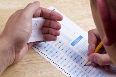 Estudiante usando un cheat sheet hacer trampa en su prueba. Foto de archivo