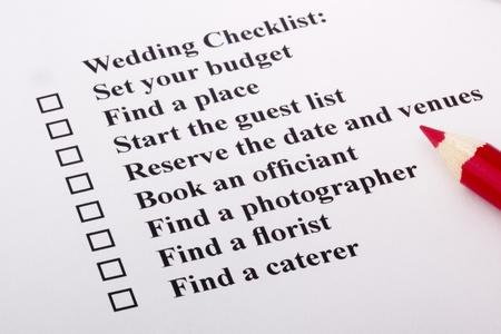 Red pencil laying on a wedding checklist. Zdjęcie Seryjne