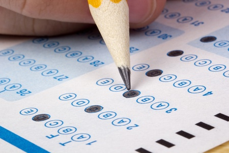 cognition: Student filling out answers to a test with a pencil.