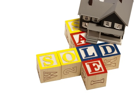 sold small: House model next to blocks spelling out the word sale and sold. Stock Photo