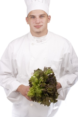 The young chef in uniform and chefs hat holding a lettuce leaf.