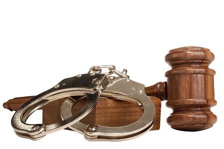 derecho penal: Martillo y esposas aisladas en un fondo blanco.