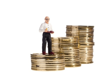 Toy of an elderly man standing on a stack of coins on a white background, representing the concept of retirement. Stock Photo - 9760024