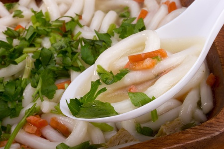 Asian noodle soup in a wooden bowl and a white spoon. photo