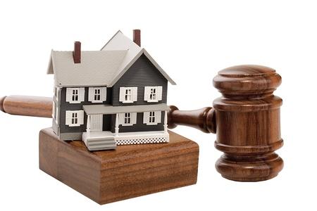 Hamer en huis model geïsoleerd op een witte achtergrond.