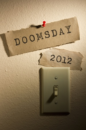 Old papers with the words Doomsday and 2012 next to a light switch representing the end of the world. photo