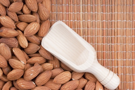 Nuts Almond are scattered as a background on a wooden mat.
