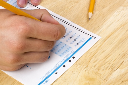 Student filling out answers to a test with a pencil. photo