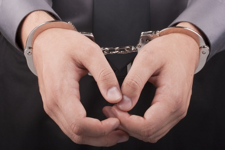 confiscation: Arrest, close-up shot mans hands with handcuffs.