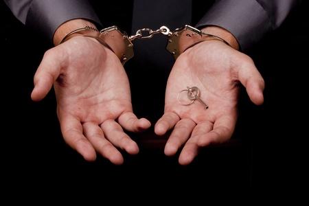 manacles: Detenido en esposas en sus manos la clave de las esposas.