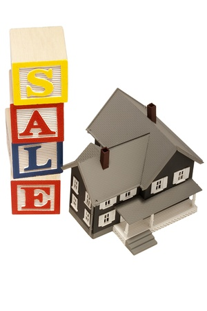sold small: House model next to blocks spelling out the word sale.