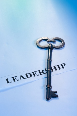 A key laying on a piece of paper with the word leadership on it.