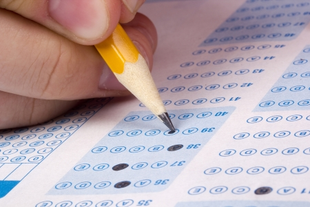 school test: Student filling out answers to a test with a pencil.