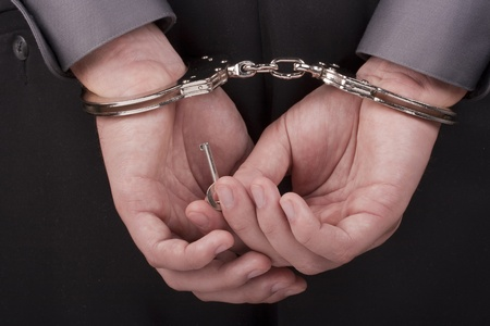 manacle: Arrested trying to rid themselves from the handcuffs with a key. Stock Photo