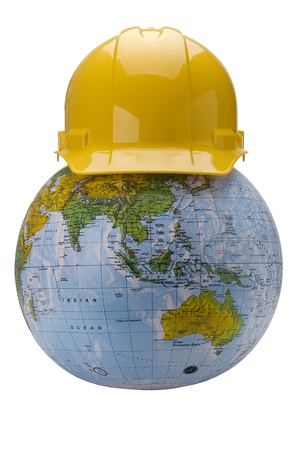 hard: Yellow hard hat on a globe isolated on a white background. Stock Photo