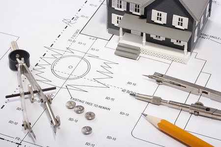architect tools: House model and drafting tools on a construction plan.