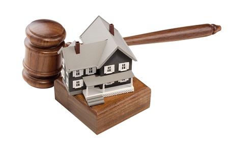 Gavel and house model isolated on a white background. photo