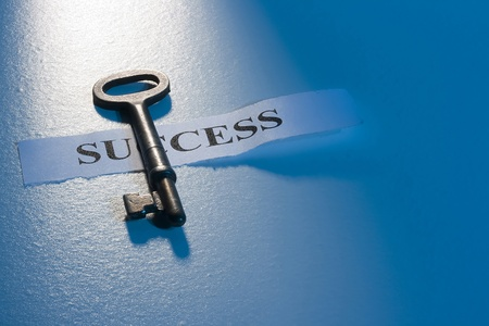 keys to success: A key laying on a piece of paper with the word success on it. Stock Photo