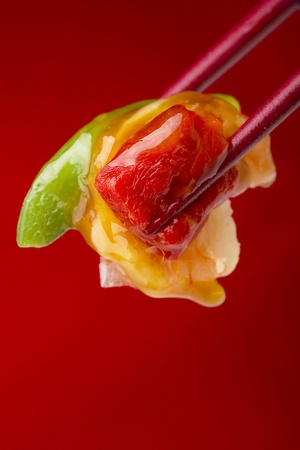 chinese culture: Food from an Asian appetizer in red chopsticks on a red background. Stock Photo