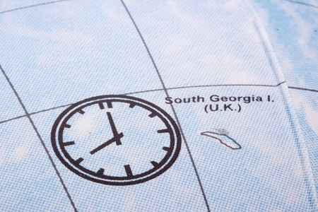 Close-up photograph of a clock on a globe. photo