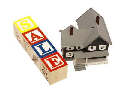 House model next to blocks spelling out the word sale.