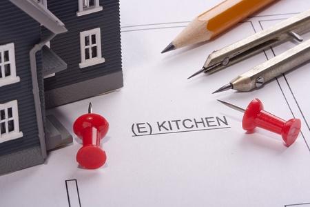 House model and drafting tools on a kitchen construction plan. photo