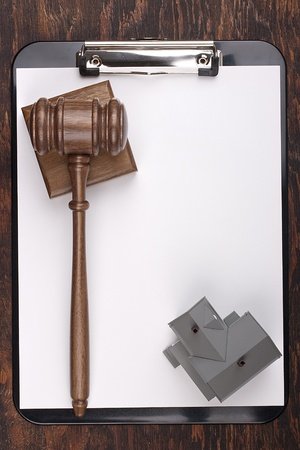 Justice gavel and house model on a clipboard. Add your text to the paper. Фото со стока