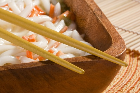 chunky: Golden chopsticks laying on a bowl of Asian noodle soup. Stock Photo