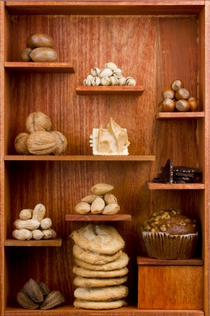 Assortment of different nuts and foods with nuts in them in a wooden shelf. photo