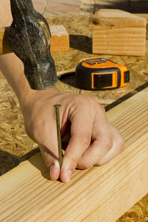 hammering: Construction worker hammering a nail into a piece of wood.