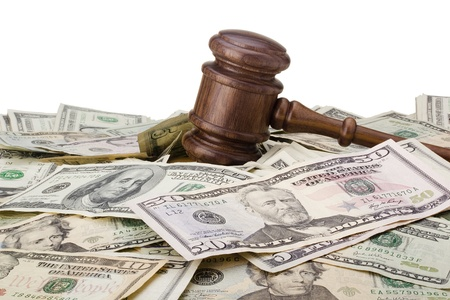 mallet: Law gavel laying on various denominations of American money.