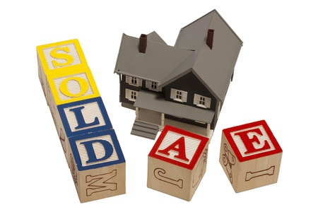 House model next to blocks spelling out the word sold.