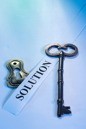 solve problems: A key laying on a piece of paper with the word solution on it.