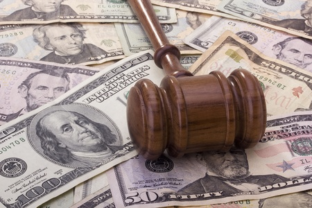 settlements: Law gavel laying on various denominations of American money.