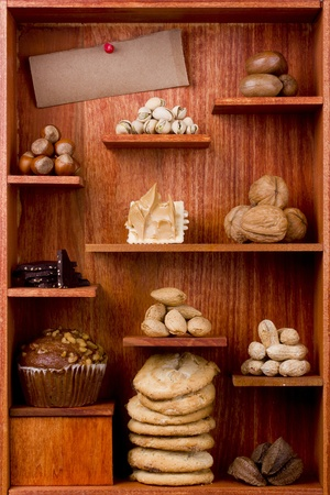 arachis: Assortment of different nuts and foods with nuts in them in a wooden shelf. Add your text to the brown paper. Stock Photo