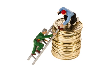 Toy men working on a stack of golden coins isolated on a white background. Stock Photo - 10882163